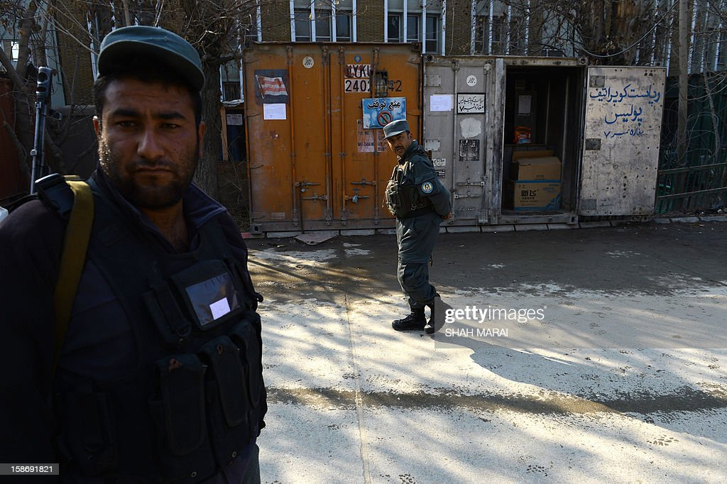 Afghan policemen stand guard at the site where a female police officer shot dead a foreign civilian adviser at police headquarters in Kabul on December 24, 2012. A female Afghan police officer has shot dead a foreign civilian adviser in Kabul police headquqarers in an apparent 'green on blue' attack, the first of its kind by a woman, officials said. AFP PHOTO/ SHAH Marai