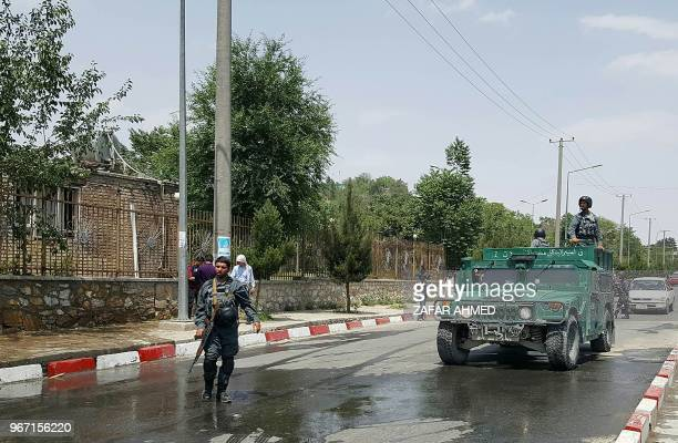 Afghan policemen stand guard near the site of a suicide attack at the gates of Kabul's Polytechnic University in Kabul on June 4 2018 At least seven...