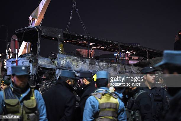 Afghan policemen stand next to the burned out wreckage of an army bus at the scene of a suicide attack in Kabul on December 13 2014 A suicide attack...