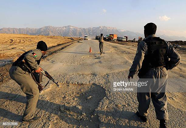 Afghan policemen stop a vechile near the site of a suicide attack outside Bagram Air base, 50 kms north of Kabul on March 4, 2009. A twin attack...