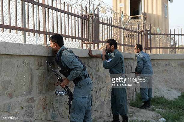 Afghan policemen take cover near the site of a suicide attack in front of Kabul's military airport on July 17 2014 Explosions and gunfire rang out...