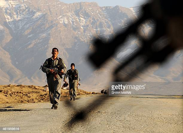 Afghan policemen walk near the site of a suicide attack outside Bagram Air base 50 kms north of Kabul on March 4 2009 A twin attack involving a car...