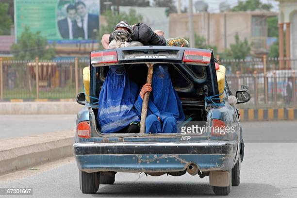 Afghan polio vaccination volunteers ride in the open trunk of a car as they travel to administer the vaccine during a campaign in Dehdaadi district...