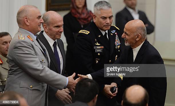 Afghan President Ashraf Ghan shakes hands with deputy commander of the NATOled International Security Assistance Force German Army Lt General Carsten...
