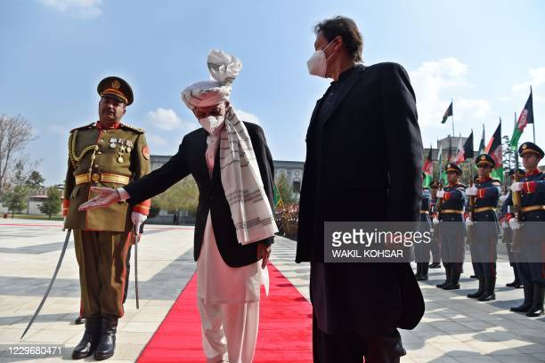 Afghan President Ashraf Ghani gestures to Pakistan's Prime Minister Imran Khan during a guard of honour ahead of their joint press conference at the...