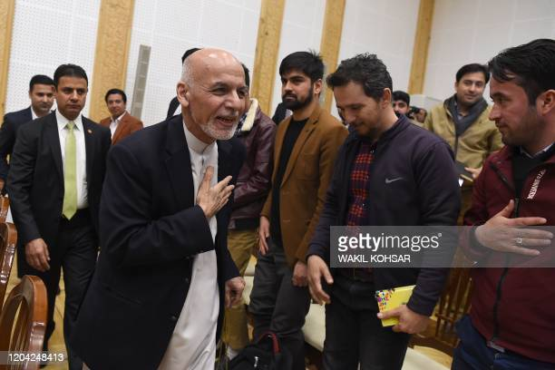 Afghan President Ashraf Ghani greets journalists after a press conference at the presidential palace in Kabul on March 1, 2020.
