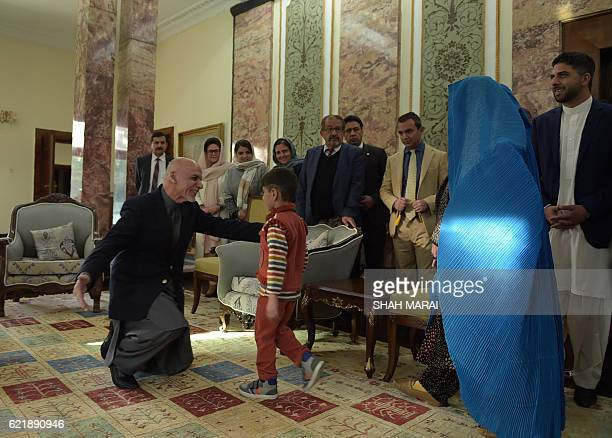Afghan President Ashraf Ghani greets the son of refugee Sharbat Gula at the Presidential Palace in Kabul on November 9 2016 An Afghan woman...