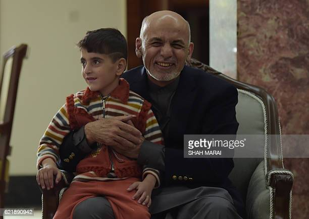 Afghan President Ashraf Ghani holds the son of refugee Sharbat Gula at the Presidential Palace in Kabul on November 9 2016 An Afghan woman...
