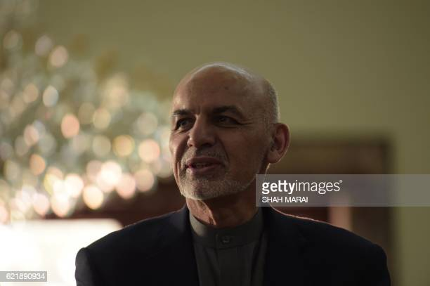 Afghan President Ashraf Ghani looks on as he speaks with Sharbat Gula at the Presidential Palace in Kabul on November 9 2016 An Afghan woman...
