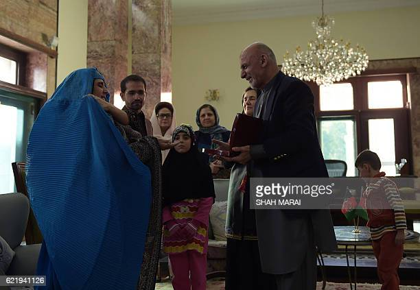 Afghan President Ashraf Ghani presents Afghan refugee Sharbat Gula with a key to a new apartment at the Presidential Palace in Kabul on November 9...