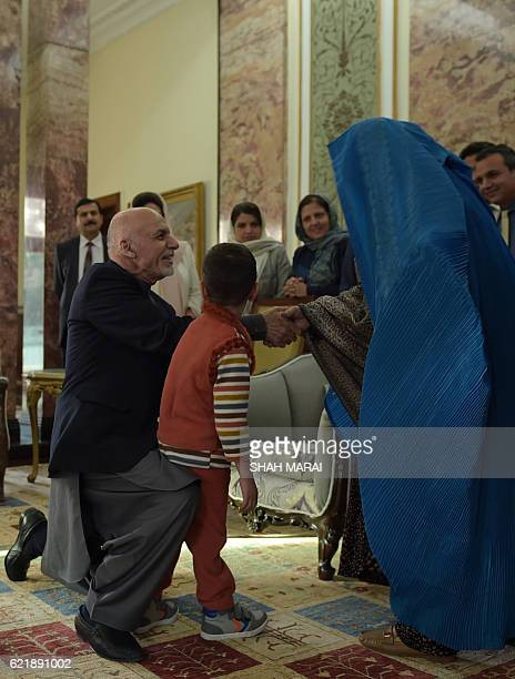Afghan President Ashraf Ghani shakes hands with Afghan refugee Sharbat Gula at the Presidential Palace in Kabul on November 9 2016 An Afghan woman...