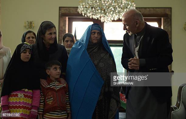 TOPSHOT Afghan President Ashraf Ghani talks with Afghan refugee Sharbat Gula as First Lady Rula Ghani looks on at the Presidential Palace in Kabul on...