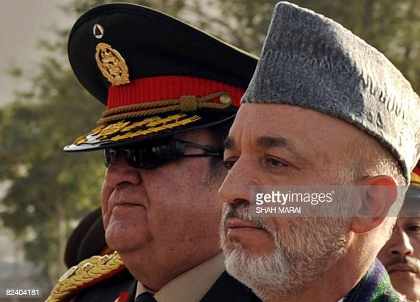 Afghan President Hamid Karzai and Afghan Defence Minister Abdul Rahim Wardak stand in a attention during a ceremony marking the anniversary of...