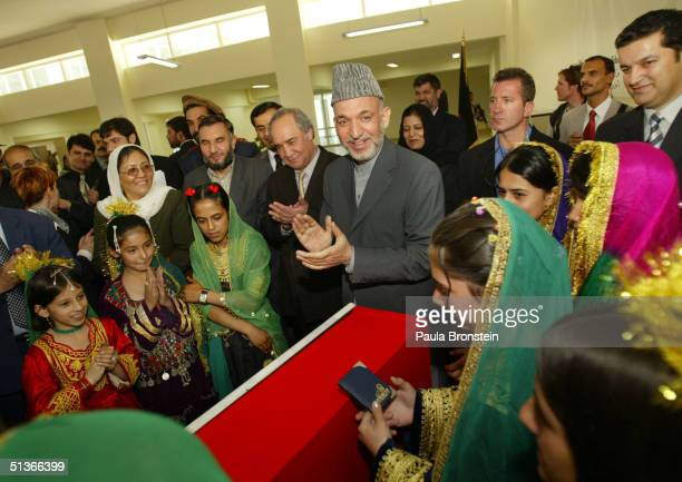Afghan President Hamid Karzai applauds during a ceremony at Kabul University for the opening of the National Women's Dormitory September 28, 2004 in...