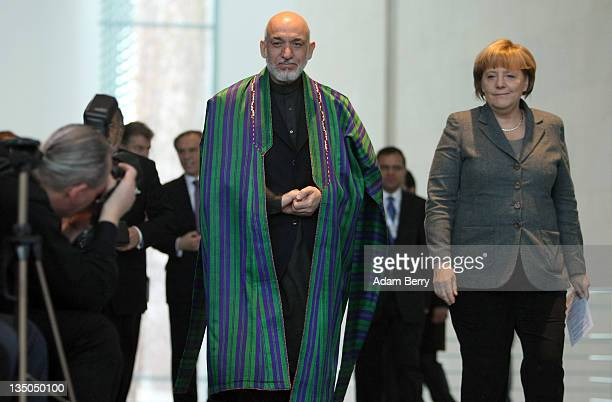 Afghan president Hamid Karzai arrives with German Chancellor Angela Merkel for a news conference in the German federal chancellery on December 6,...