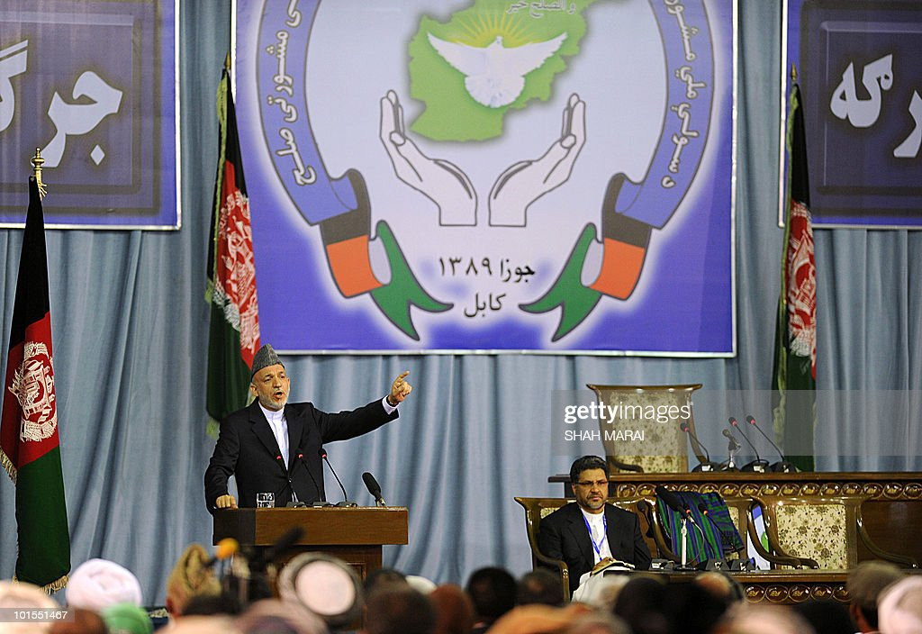 Afghan President Hamid Karzai (L) delivers a speech to the National Consultive Peace Jirga in Kabul on June 2, 2010. The Taliban claimed responsibility for a series of attacks on a landmark gathering in the Afghan capital, where hundreds of delegates are meeting to discuss peace talks. 'We have four suicide attackers placed on the top of a tall building near the jirga tent. They are threatening the jirga tent,' Zabihullah Mujahid, a Taliban spokesman, told AFP by telephone.AFP PHOTO/SHAH Marai