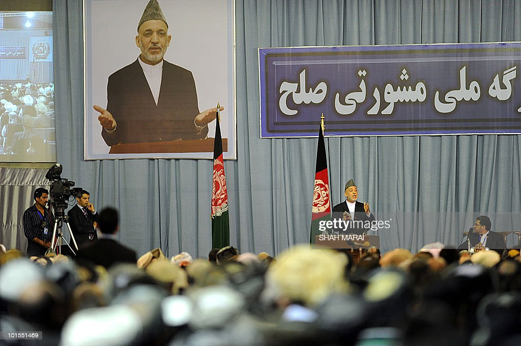 Afghan President Hamid Karzai (2R) delivers a speech to the National Consultive Peace Jirga in Kabul on June 2, 2010. The Taliban claimed responsibility for a series of attacks on a landmark gathering in the Afghan capital, where hundreds of delegates are meeting to discuss peace talks. 'We have four suicide attackers placed on the top of a tall building near the jirga tent. They are threatening the jirga tent,' Zabihullah Mujahid, a Taliban spokesman, told AFP by telephone.AFP PHOTO/SHAH Marai