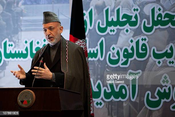 Afghan President Hamid Karzai gestures as he speaks during a gathering to mark the seventh adoption year of Afghanistan's post-Taliban Constitution...