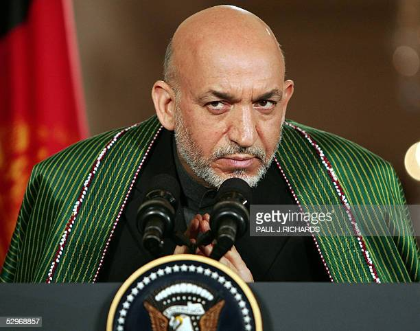 Afghan President Hamid Karzai listens to a reporter's question as he and US President George W. Bush conduct a joint press conference in the East...