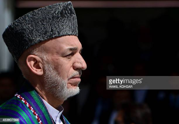 Afghan President Hamid Karzai looks on during an event to mark Independence Day at the Ministry of Defence compound in Kabul on August 19, 2014....