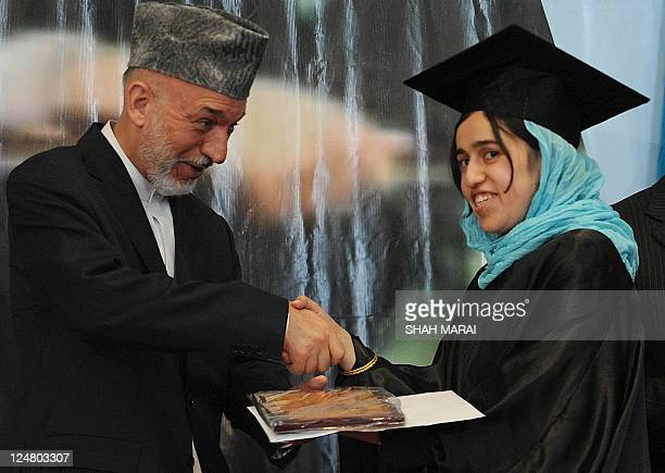 Afghan President Hamid Karzai shakes hands with a female student during a graduation ceremony of university students in Kabul on September 13 2011...