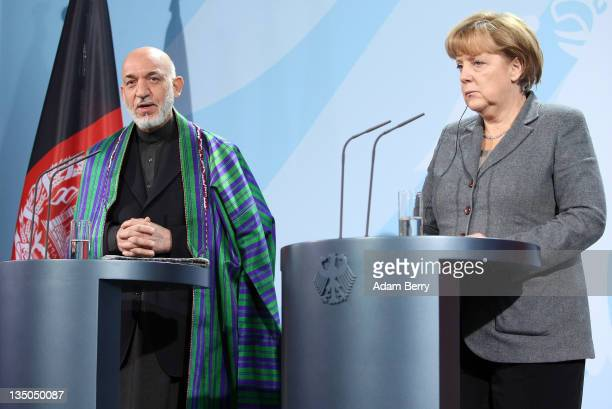 Afghan president Hamid Karzai speaks next to German Chancellor Angela Merkel during a news conference in the German federal chancellery on December...