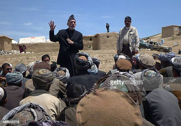 Afghan President Hamid Karzai talks with displaced villagers during a visit to the site of a deadly landslide in Aab Bareek village in the Argo...
