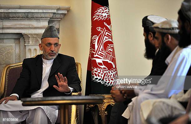 Afghan President Hamid Karzai talks with families of two men who were beheaded by Pakistani militants, at The Presidential Palace in Kabul on July...