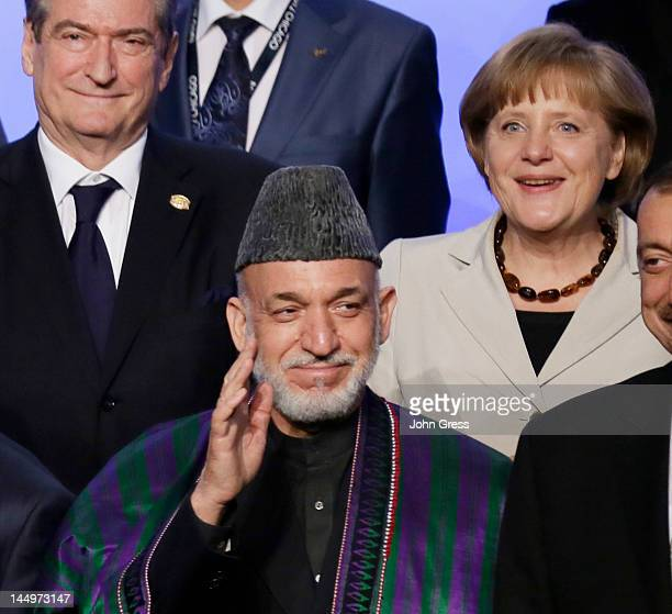 Afghan President Hamid Karzai waves as German Chancellor Angela Merkel and Albanian Prime Minister Sali Berisha look during a group photo at the NATO...