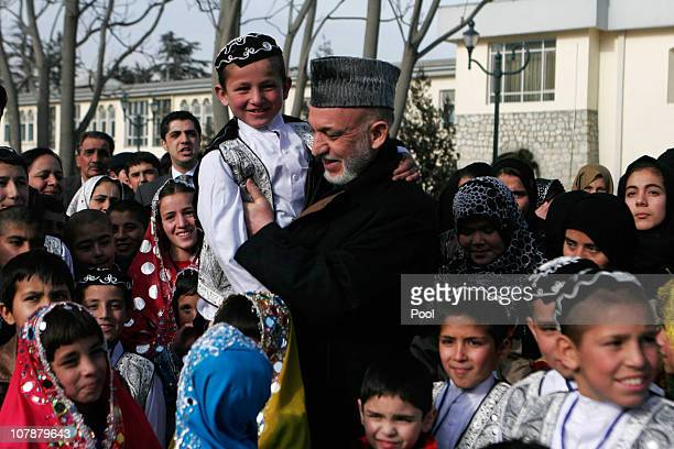 Afghan President Hamid Karzi, center, holds an afghan orphan boy as other orphans looks on during a vist to Presidential Palace on January 5, 2010 in...