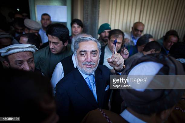 Afghan presidential candidate Abdullah Abdullah holds up his inked finger as he speaks to media after casting his vote at a polling station on June...