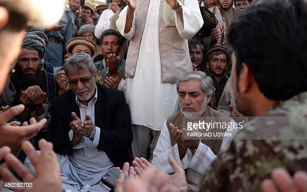 Afghan presidential candidate Abdullah Abdullah prays with Afghan residents affected by the flood in a camp for flood victims in the Guzirga iNur...