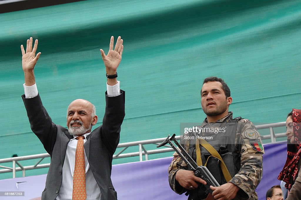 Afghan Presidential Candidate Ashraf Ghani Ahmadzai holds up his arms beside a soldier at a rally for thousands of supporters at the Ghazi stadium on April 1, 2014 in Kabul, Afghanistan. Mr. Ghani is a frontrunner in the April 5 vote to succeed President Hamid Karzai, in an election that is seen as a test of stability that will ensure continued Western donor aid for a nation torn by a Taliban insurgency. The Ghazi stadium is known as the site of amputations and executions during Taliban rule in the late 1990s.