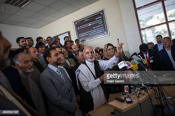 Afghan presidential candidate Ashraf Ghani holds up his inked finger as he speaks to media after casting his vote at a polling station on June 14,...