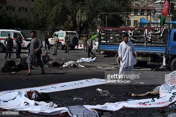 Afghan protesters walk near the bodies of victims at the scene of a suicide attack that targeted crowds of minority Shiite Hazaras during a...