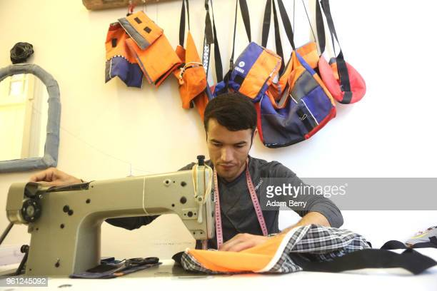 Afghan refugee Amir Mohammadi sews life preserver material and fabric together to make a bag at the Lesvos Solidarity organization's Safe Passage...