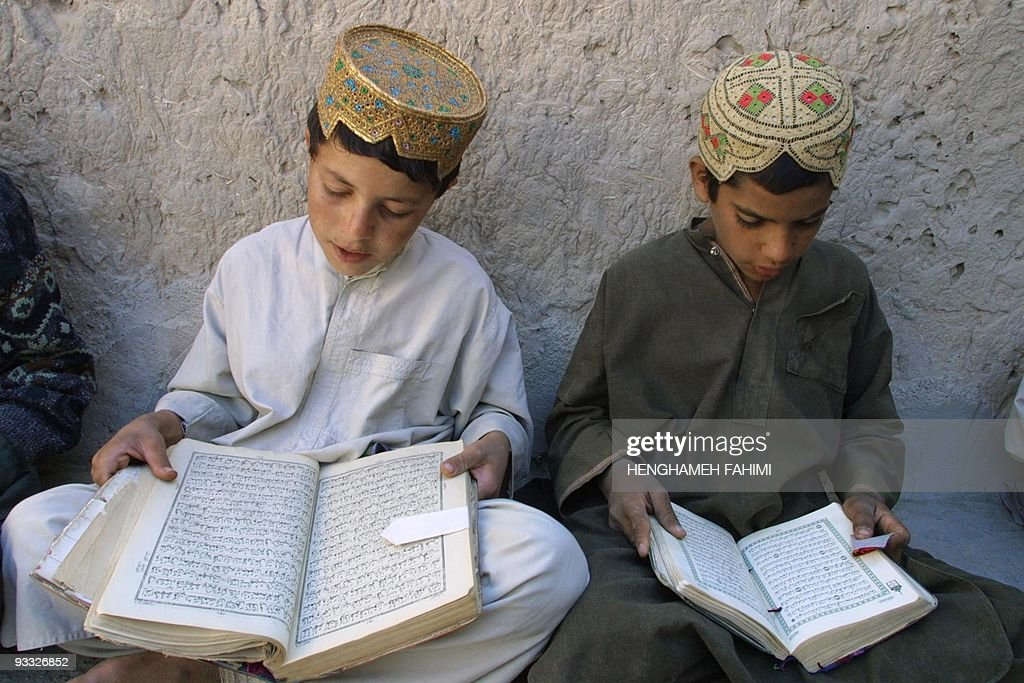 Afghan refugee boys read Islam's holy book, the Koran, during a religion class 18 October 2001 at the Kholafa-e-Rashedin mosque in the refugee camp of the Niatak, some three kms from the border with Afghanistan, near Iran's southeasten city of Zabol. The Taliban, with which Tehran has hostile relations, have opposed Iran's plan to build camps on Afghan soil for refugees from the US-Afghan conflict, according to Iran's Red Crescent chief. Iran hosts 2.5 million refugees from Afghanistan and of whom about 5,000 live in the Niatak camp, receiving food from Iranian and foreign relief agencies. AFP PHOTO/Henghameh FAHIMI