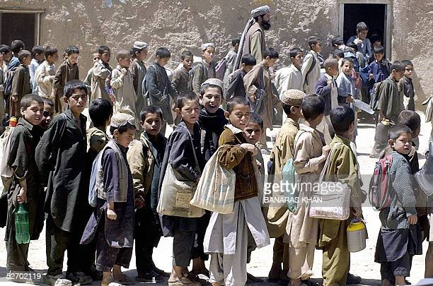 Afghan refugee children gather outside their classrooms at a school at the Saranan refugee camp, some 45 kilometers northwest of Quetta, 27 April...