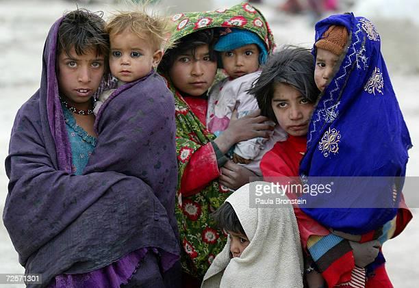 Afghan refugee children huddle together to shelter from the cold October 12, 2004 at the Babrak Garden Refugee camp in Kabul, Afghanistan. Over 150...