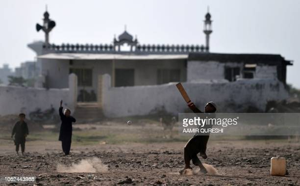Afghan refugee children play cricket at a refugee camp in Islamabad on October 18 2018
