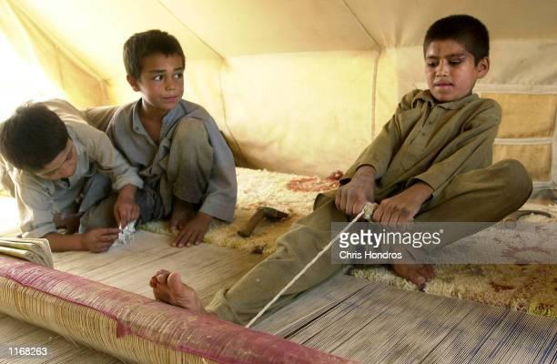 Afghan refugee children work together to weave a rug October 24 2001 at the Shamshatu refugee camp in Pakistan The boys make carpets to raise money...