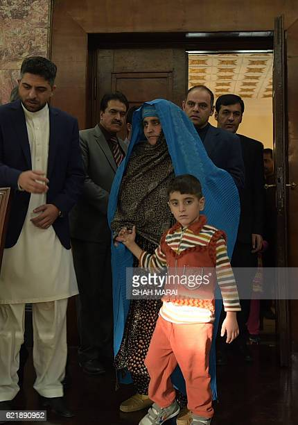 Afghan refugee Sharbat Gula arrives with her son before meeting with Afghan President Ashraf Ghani at the Presidential Palace in Kabul on November 9...