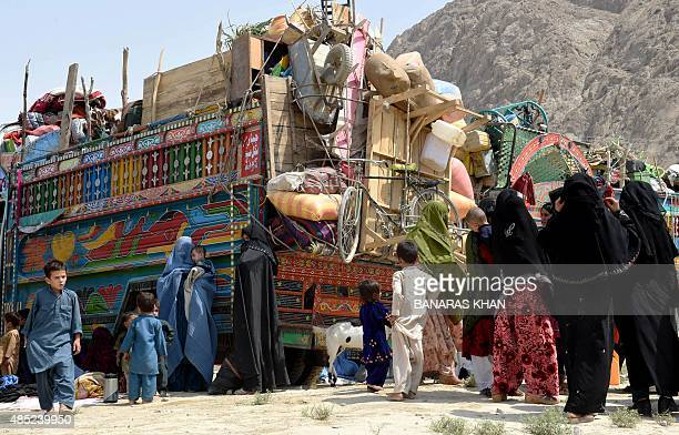 Afghan refugee women and children gather beside loaded trucks at the United Nations High Commissioner for Refugees repatriation centre on the...