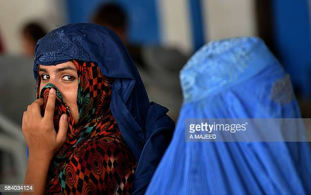 TOPSHOT Afghan refugee women wait to board trucks at the United Nations High Commissioner for Refugees repatriation centre on the outskirts of...