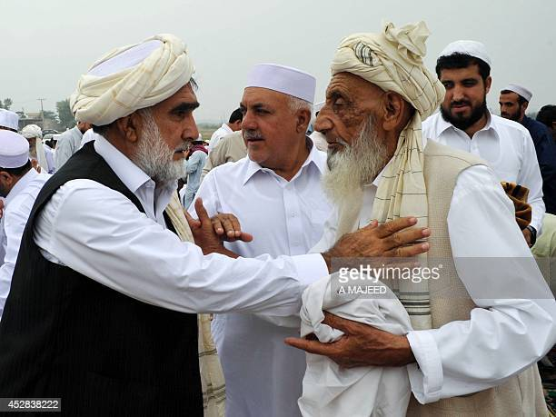 Afghan refugees and Pakistani men exchange Eid greetings after offering Eid alFitr prayers at the end of the fasting month of Ramadan on the...