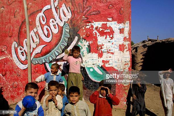 Afghan refugees children play in front of a CocaCola sign painted on the wall of a house in their refugee village Kachagari in Pakistani Northwest...