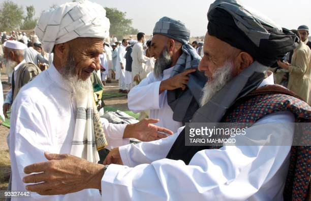 Afghan refugees exchange Eid greetings after they offered 'Eid alFitr' prayers at a refugee camp near Peshawar on September 30 2008 Millions of...