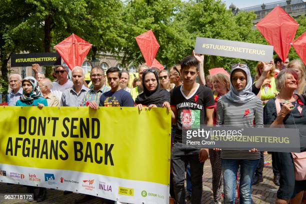 Afghan refugees hold banners as human rights group Amnesty International hands over a petition signed by more the 68000 people to the Dutch...