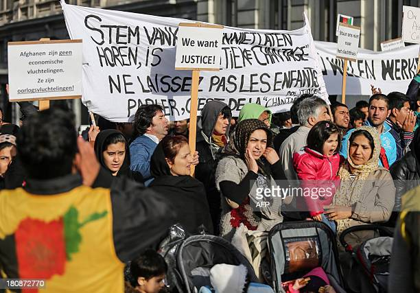 Afghan refugees hold signs as they demonstrate against Belgian State Secretary of Home Affairs Maggie De Block's policy near the Wetstraat street in...