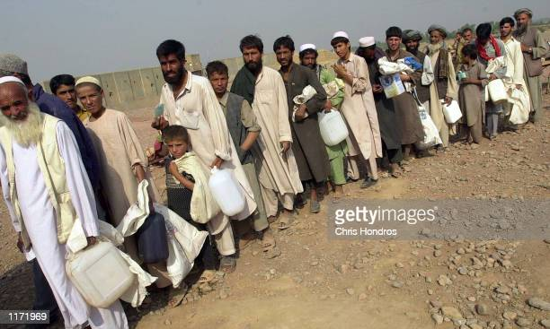 Afghan refugees line up for cooking oil during a food disbursement at the Shamshatu refugee camp October 22, 2001 in Pakistan near the border with...